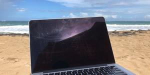 laptop screen on a beach, with sand and waves behind it.